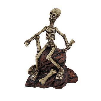 Жуткий скелет, сидя на скалах статуя фигура