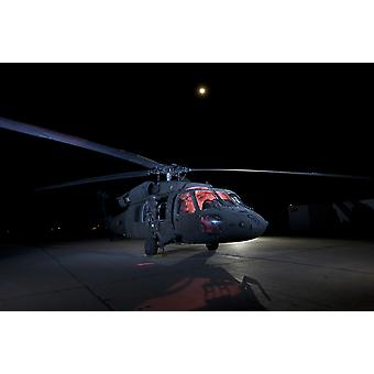 A UH-60 Black Hawk helicopter lit up by multiple flash units under a full moon Poster Print