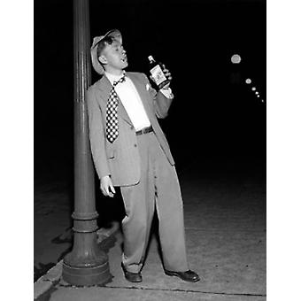 Drunk mid adult man leaning against a lamppost holding a bottle of alcohol Poster Print